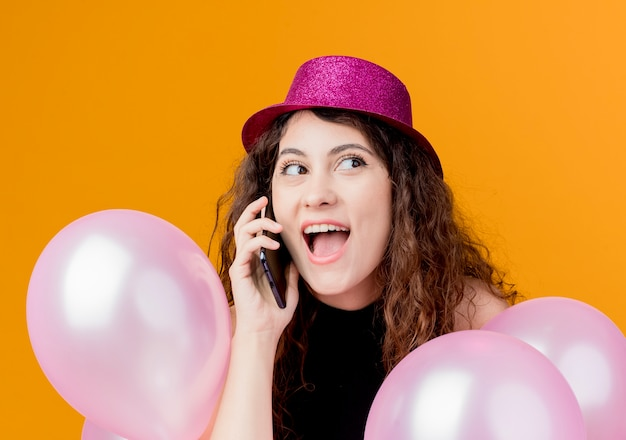 Junge schöne frau mit lockigem haar in einem feiertagshut, der bündel luftballons spricht, die auf dem glücklichen und aufgeregten geburtstagsfeierkonzept des mobiltelefons über orange wand stehen