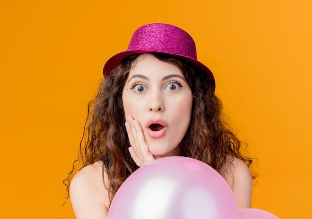 Junge schöne frau mit lockigem haar in einem feiertagshut, der bündel von luftballons hält, überraschte und verblüffte geburtstagsfeierkonzept über orange