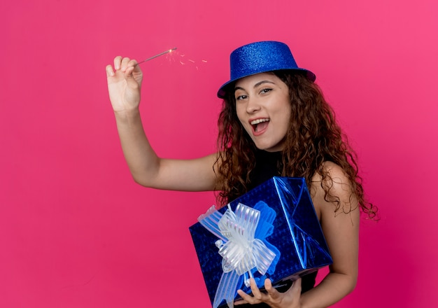 Junge schöne frau mit lockigem haar in einem feiertagshut, der geburtstagsgeschenkbox und wunderkerze glücklich und aufgeregt geburtstagsfeierkonzept über rosa hält