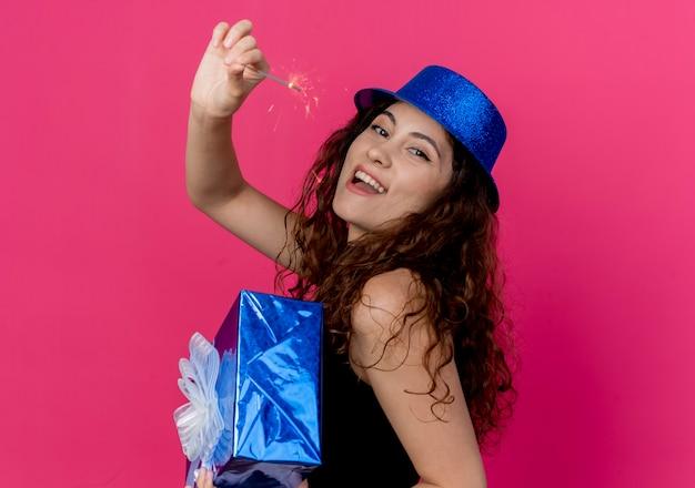 Junge schöne frau mit lockigem haar in einem feiertagshut, der geburtstagsgeschenkbox und wunderkerzenglück- und aufgeregtes geburtstagsfeierkonzept hält, das über rosa wand steht