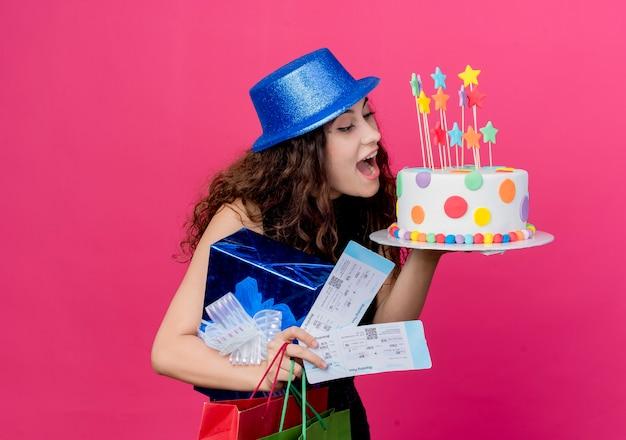 Junge schöne frau mit lockigem haar in einem feiertagshut, der geburtstagskuchen-geschenkbox und flugkarten-glückliches und aufgeregtes geburtstagsfeierkonzept hält, das über rosa wand steht
