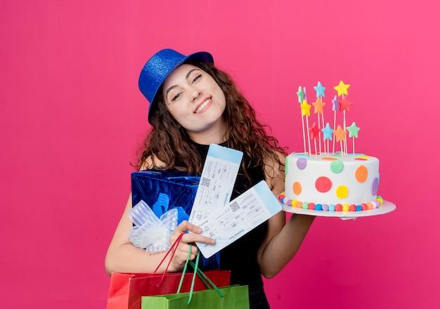 Junge schöne frau mit lockigem haar in einem feiertagshut, der geburtstagskuchen-geschenkbox und flugtickets glücklich und erfreut lächelt fröhlich geburtstagsfeierkonzept über rosa