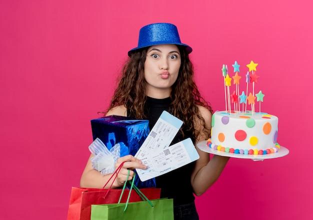 Junge schöne frau mit lockigem haar in einem feiertagshut, der geburtstagskuchen-geschenkbox und flugtickets glückliches und positives geburtstagsfeierkonzept hält, das über rosa wand steht