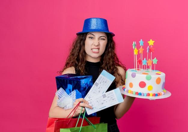 Junge schöne frau mit lockigem haar in einem feiertagshut, der geburtstagskuchen-geschenkbox und flugtickets hält, die verwirrtes und missfallenes geburtstagsfeierkonzept stehen, das über rosa wand steht