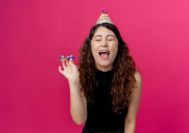 Junge schöne frau mit lockigem haar in einem feiertagskappen-verrückten alles gute zum geburtstagsfeierkonzept, das über rosa wand steht