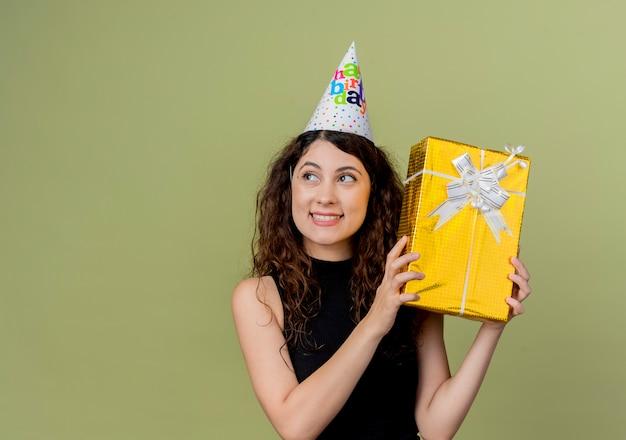 Junge schöne frau mit lockigem haar in einer feiertagskappe, die geburtstagsgeschenk glücklich und positives geburtstagsfeierkonzept hält, das über lichtwand steht