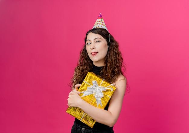 Junge schöne frau mit lockigem haar in einer feiertagskappe, die geburtstagsgeschenkbox hält, die fröhlich herausragt zunge geburtstagsfeierkonzept steht über rosa wand