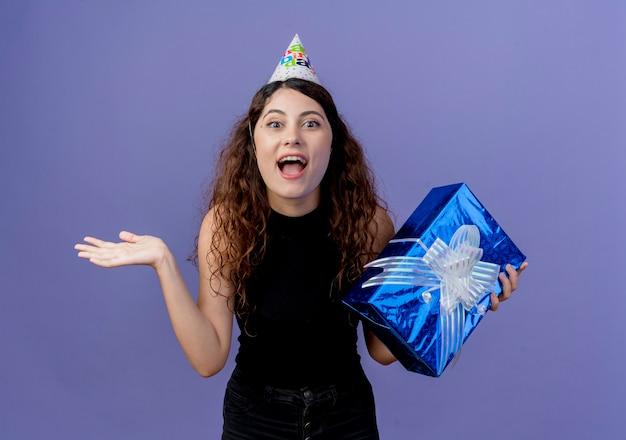 Junge schöne frau mit lockigem haar in einer feiertagskappe, die geburtstagsgeschenkbox hält, die verwirrt und überrascht lächelnd fröhlich geburtstagsfeierkonzept steht, das über blauer wand steht