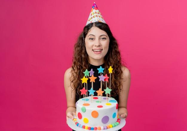 Junge schöne frau mit lockigem haar in einer feiertagskappe, die geburtstagskuchen glücklich und aufgeregt lächelndes geburtstagsfeierkonzept hält über rosa wand hält