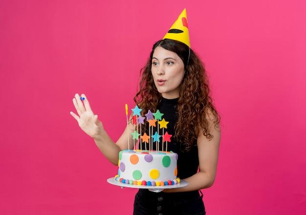 Junge schöne frau mit lockigem haar in einer feiertagskappe, die geburtstagskuchen glückliches und positives geburtstagsfeierkonzept hält über rosa wand hält