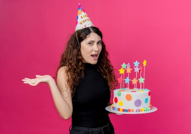 Junge schöne frau mit lockigem haar in einer feiertagskappe, die geburtstagskuchen hält, verwirrte geburtstagsfeierkonzept, das über rosa wand steht
