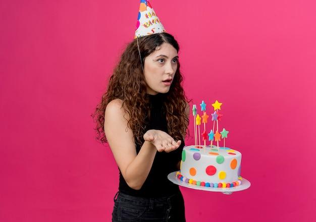 Junge schöne frau mit lockigem haar in einer feiertagskappe, die geburtstagstorte hält, die beiseite mit arm heraus verwirrt betrachtet, als geburtstagsfeierkonzept über rosa fragend