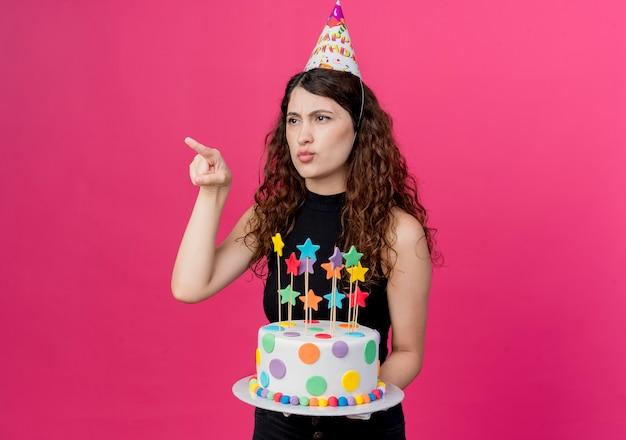 Junge schöne frau mit lockigem haar in einer feiertagskappe, die geburtstagstorte hält, die mit finger auf etwas zeigt, das unzufriedenes geburtstagsfeierkonzept steht, das über rosa wand steht
