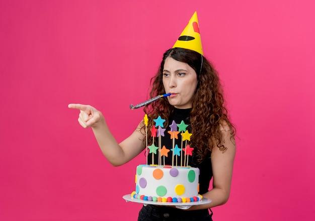 Junge schöne frau mit lockigem haar in einer feiertagskappe, die geburtstagstorte hält, die pfeife zeigt, zeigt mit dem finger zur seite, die unzufriedenes geburtstagsfeierkonzept steht, das über rosa wand steht