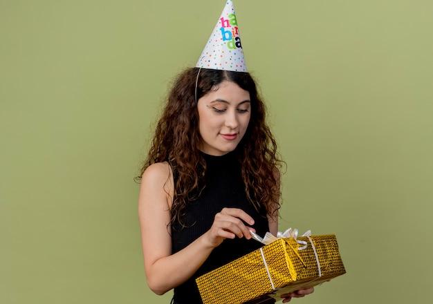 Junge schöne frau mit lockigem haar in einer feiertagskappe, die geschenkbox hält, die es mit lächeln auf gesichtgeburtstagsfeierkonzept betrachtet, das über lichtwand steht