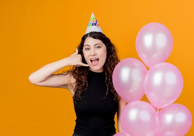 Junge schöne frau mit lockigem haar in einer feiertagskappe, die luftballons glücklich und positiv zeigt, rufen mich gestengeburtstagsfeierkonzept an, das über orange wand steht