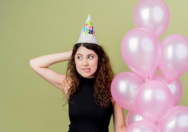 Junge schöne frau mit lockigem haar in einer feiertagskappe, die luftballons hält, die beiseite lächelndes beißendes lippengeburtstagsfeierkonzept über licht suchen