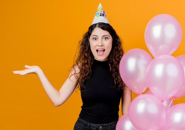 Junge schöne frau mit lockigem haar in einer feiertagskappe, die luftballons hält, die etwas mit dem arm der hand glücklich und aufgeregt geburtstagsfeierkonzept über orange präsentieren