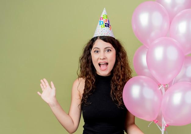 Junge schöne frau mit lockigem haar in einer feiertagskappe, die luftballons hält, die glückliches und aufgeregtes lächelndes fröhliches geburtstagsfeierkonzept der hand anheben, das über lichtwand steht
