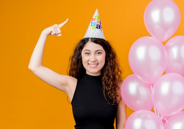 Junge schöne frau mit lockigem haar in einer feiertagskappe, die luftballons hält, die glückliches und positiv lächelndes geburtstagsfeierkonzept des zeigefingers zeigen, das über orange wand steht