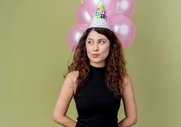 Junge schöne frau mit lockigem haar in einer feiertagskappe, die luftballons hält, die glückliches und positives geburtstagsfeierkonzept beiseite stehen, das über lichtwand steht