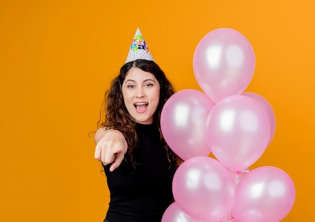 Junge schöne frau mit lockigem haar in einer feiertagskappe, die luftballons hält, die mit dem finger an der kamera zeigen, die fröhlich geburtstagsfeierkonzept über orange lächelt
