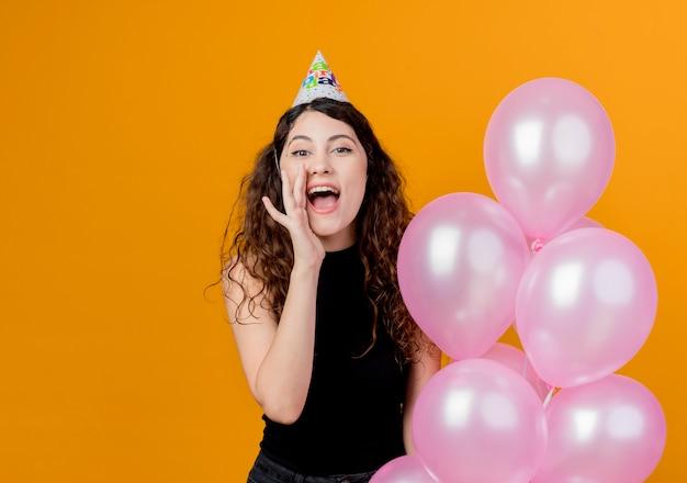 Junge schöne frau mit lockigem haar in einer feiertagskappe, die luftballons hält, die mit hand nahe mundgeburtstagsfeierkonzept über orange schreien oder rufen