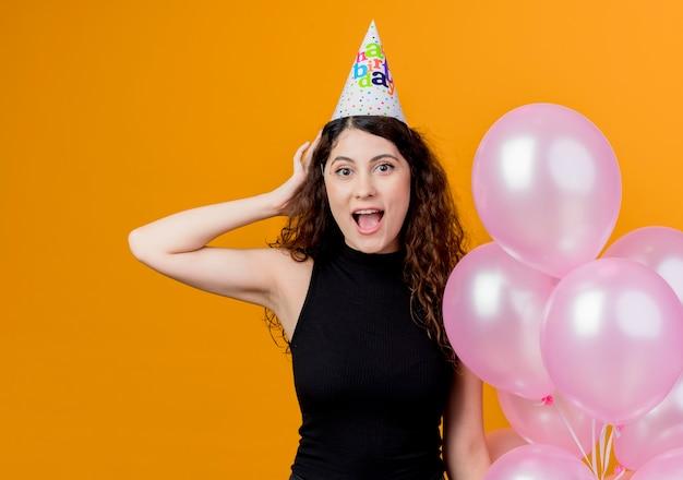 Junge schöne frau mit lockigem haar in einer feiertagskappe, die luftballons überrascht und alles gute zum geburtstagfeierkonzept hält, das über orange wand steht