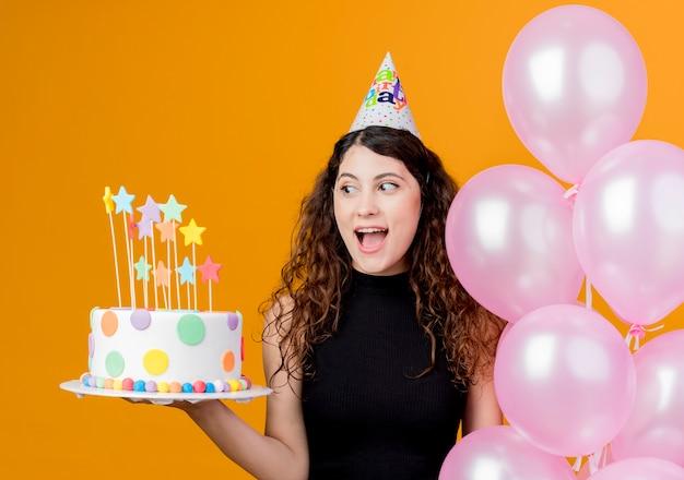 Junge schöne frau mit lockigem haar in einer feiertagskappe, die luftballons und geburtstagskuchen-glückliches und aufgeregtes geburtstagsfeierkonzept hält, das über orange wand steht