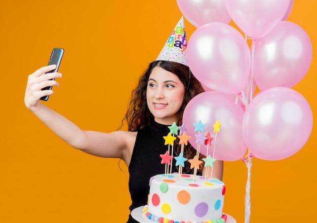 Junge schöne frau mit lockigem haar in einer feiertagskappe, die luftballons und geburtstagstorte hält, die freudig geburtstagsfeierkonzept des selfies lächelnd über orange wand hält