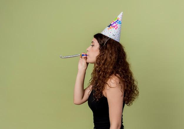 Junge schöne frau mit lockigem haar in einer feiertagskappe, die pfeifengeburtstagsfeierkonzept seitwärts über licht bläst