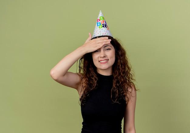 Junge schöne frau mit lockigem haar in einer feiertagskappe, die verwirrend lächelnd mit hand über kopf-geburtstagsfeierkonzept steht, das über orange wand steht