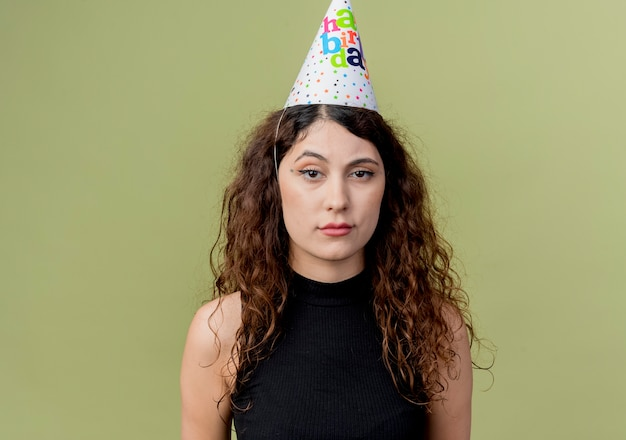 Junge schöne frau mit lockigem haar in einer feiertagskappe mit traurigem ausdruckgeburtstagsfeierkonzept über licht