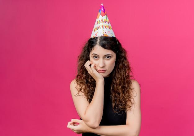 Junge schöne frau mit lockigem haar in einer feiertagskappe mit traurigem ausdruckgeburtstagsfeierkonzept über rosa