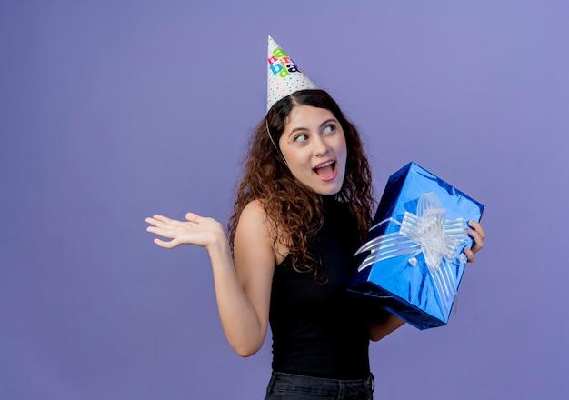 Junge schöne frau mit lockigem haar in einer feiertagsmütze, die geburtstagsgeschenkbox hält, die erstaunt und überrascht lächelt, das fröhlich geburtstagsfeierkonzept steht, das über blauer wand steht