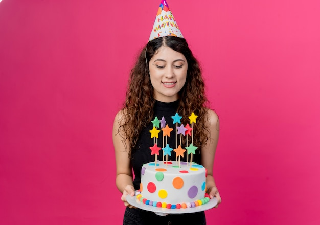 Junge schöne frau mit lockigem haar in einer feiertagsmütze, die geburtstagskuchen glücklich und positives geburtstagsfeierkonzept über rosa hält
