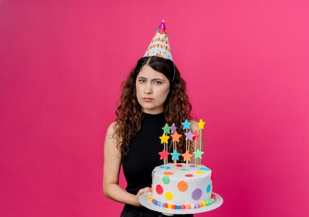 Junge schöne frau mit lockigem haar in einer feiertagsmütze, die geburtstagstorte hält, missfiel mit stirnrunzeln gesicht geburtstagsfeier konzept über rosa wand