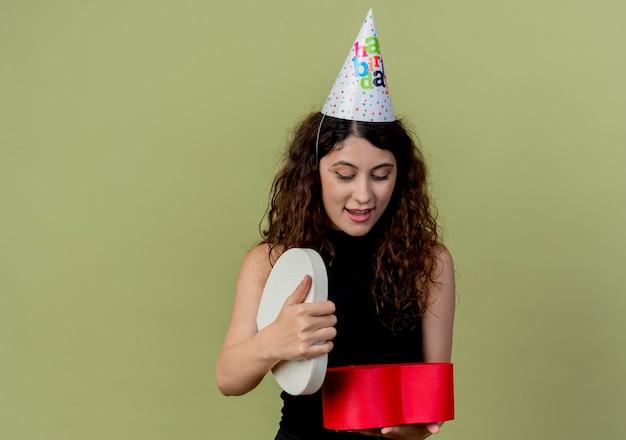 Junge schöne frau mit lockigem haar in einer feiertagsmütze, die geschenkbox hält, die es überrascht und alles gute zum geburtstagsfeierkonzept über licht betrachtet