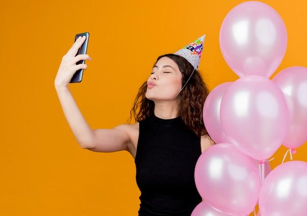 Junge schöne frau mit lockigem haar in einer feiertagsmütze, die luftballons hält, die einen kuss blasen, der selfie-geburtstagsfeierkonzept nimmt, das über orange wand steht