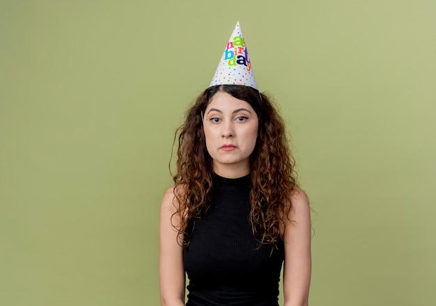 Junge schöne frau mit lockigem haar in einer feiertagsmütze mit traurigem ausdruck auf gesichtsgeburtstagsfeierkonzept, das über orange wand steht