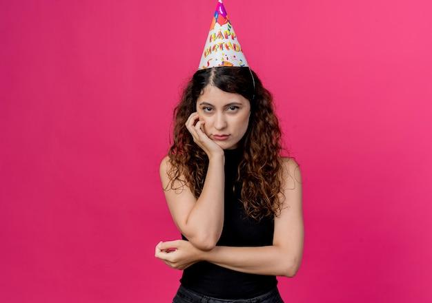 Junge schöne frau mit lockigem haar in einer feiertagsmütze mit traurigem ausdruck auf gesichtsgeburtstagsfeierkonzept über rosa