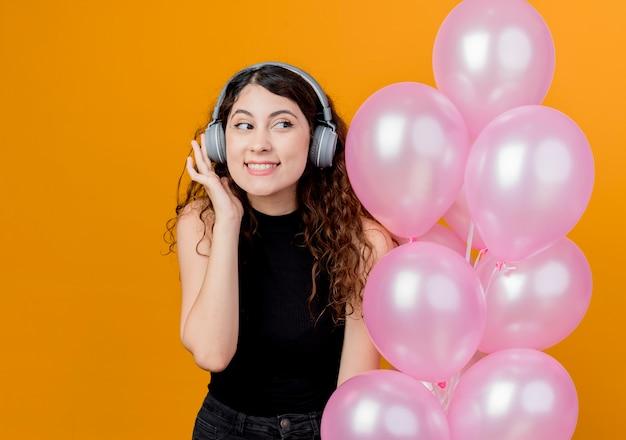 Junge schöne frau mit lockigem haar mit kopfhörern, die musik hören, die bündel luftballons glückliches und fröhliches geburtstagsfeierkonzept hält, das über orange wand steht
