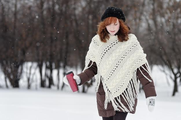 Junge schöne frau mit metallischer trommel gehend in winterpark