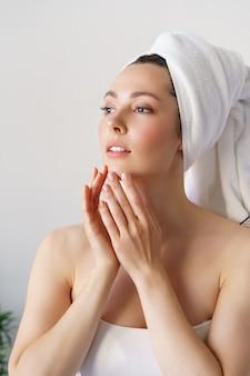 Junge schöne frau mit perfekter haut, die ihr gesicht berührt. kosmetik-, beauty- und spa-konzept.