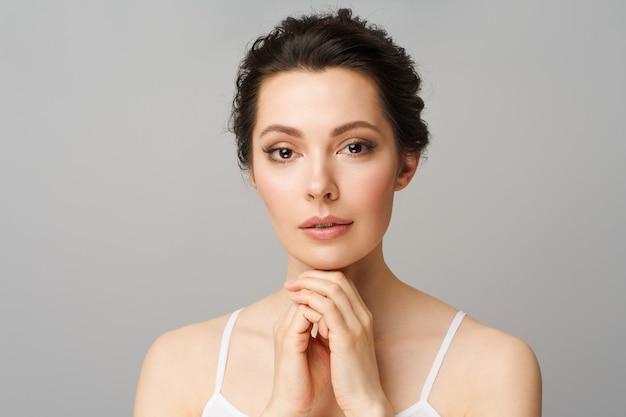 Junge schöne frau mit perfekter haut, die ihr gesicht berührt kosmetik schönheit und spa-konzept weiblich