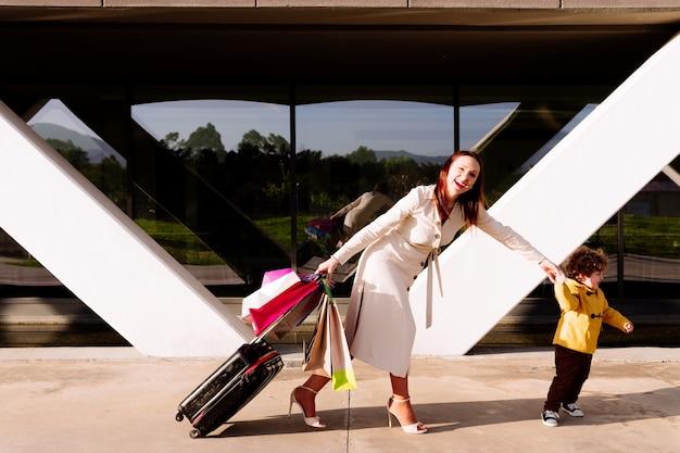 Junge schöne frau mit reisekoffer und einkaufstaschen, die von ihrem 3-jährigen sohn gezogen wurden. sie shopaholic konzept. familienreisen