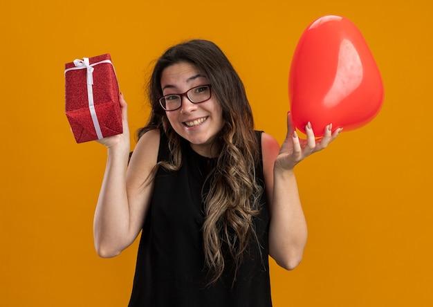 Junge schöne frau mit rotem ballon in herzform und geschenk, die überrascht und glücklich aussieht und fröhlich den valentinstag feiert