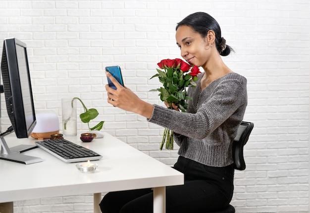 Junge schöne frau mit rotem rosenstrauß, der romantisches online-datum hat, das mit jemandem auf smartphone zu hause spricht. technologiekonzept. neue normalität. valentinstag