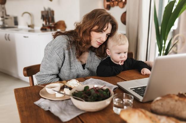 Junge schöne frau mit roten haaren im gestrickten pullover und ihrem kleinen sohn, der mit essen am tisch sitzt und cartoons auf laptop betrachtet