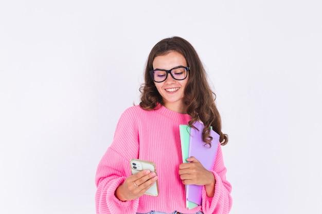 Junge schöne frau mit sommersprossen hellem make-up im pullover auf weißer wand studentin mit handy nachdenklicher blick auf bildschirm und lächeln